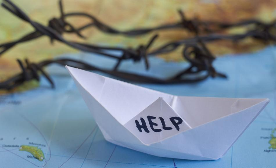 """paper boat with """"Help"""" sign on it and barbed wire ©CanStockPhoto antonchalakov"""