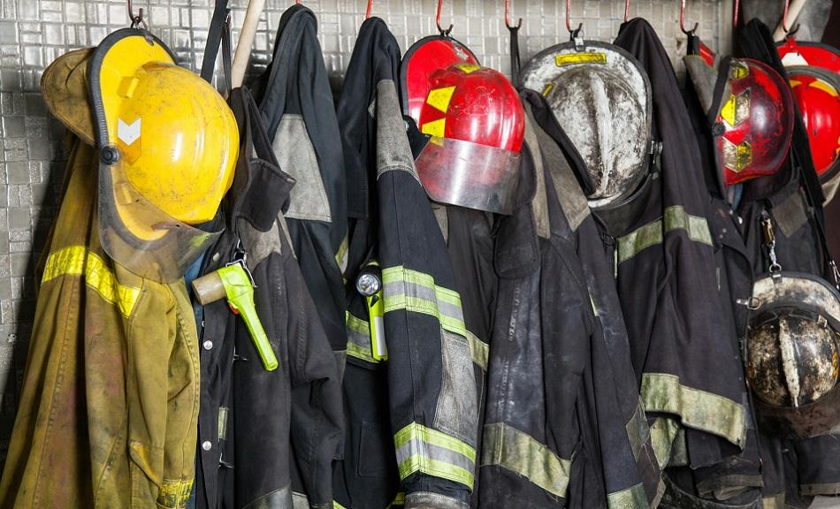 Firefighters suits and helmet hanging at fire station - working time