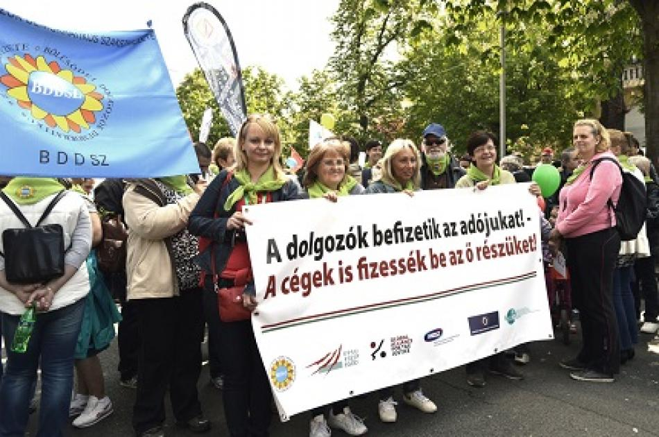 Hungarian workers of SZEF carrying the message: Working people pay taxes, corporations must pay their share