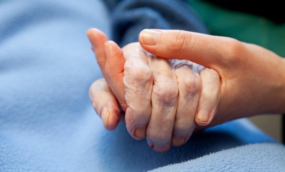 Elderly care - nurse holding hand